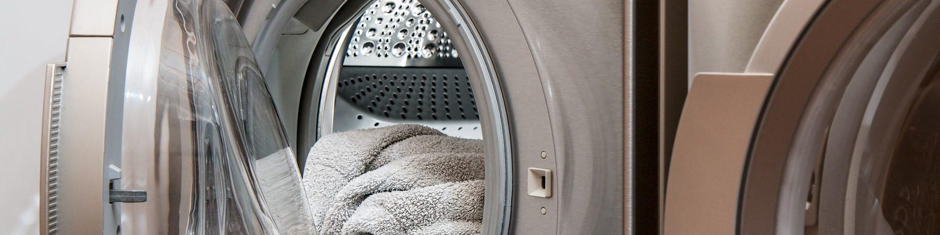 Geöffnete Waschmaschine aus der Handtücher herausragen.