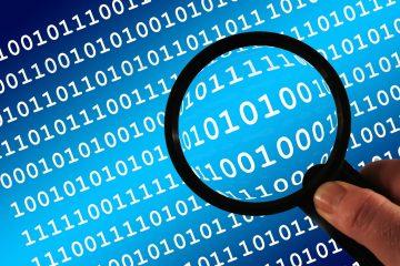 Eine Person hält eine Lupe. Die Lupe untersucht einen Biquinärcode.