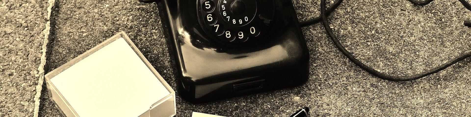 Ein altes Telefon steht auf dem Boden. Vor ihm ein Zettel und ein Stift.