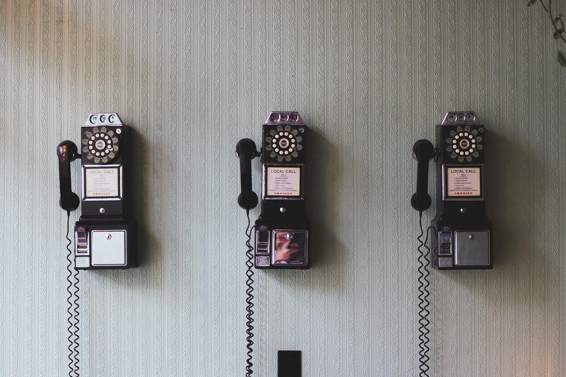 Drei alte Telefone hängen an einer Wand.