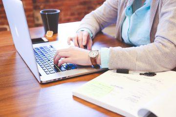 Eine Person sitzt vor einem Laptop.