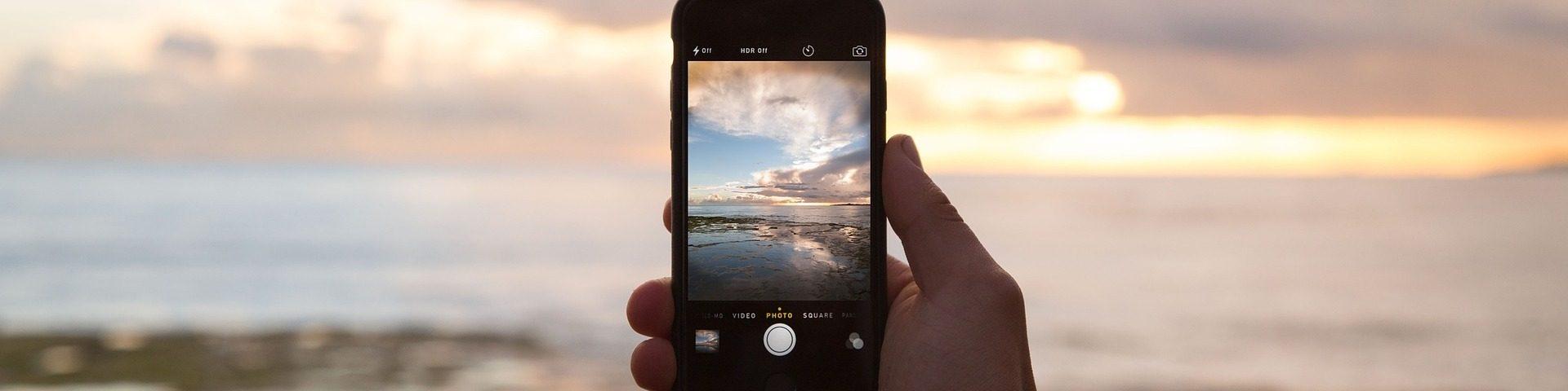 Eine Person hält ein Smartphone in die Landschaft.