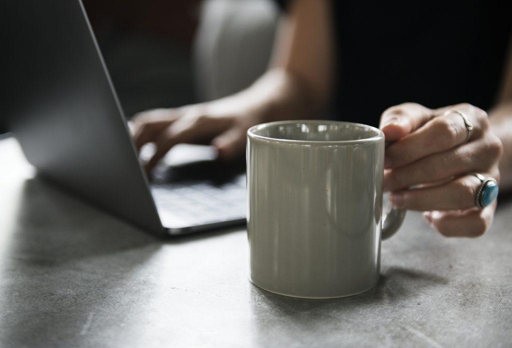 Eine Person sitzt vor einem Laptop und greift nach einer Tasse.