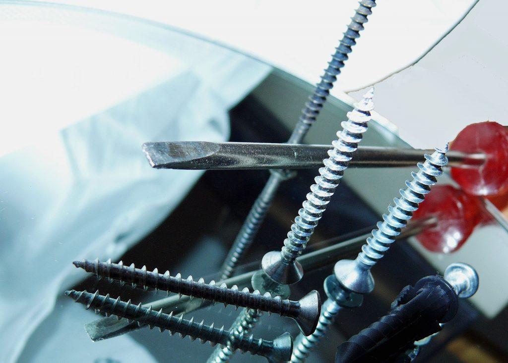 Schrauben und Schraubendreher auf einem Glastisch.