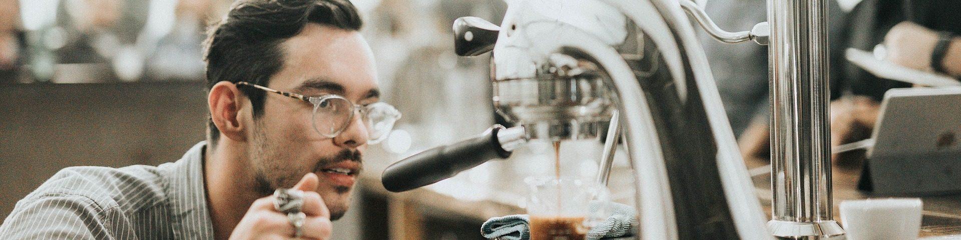 Mann mit Brille schaut sich eine Kaffeemaschine ganz genau an.