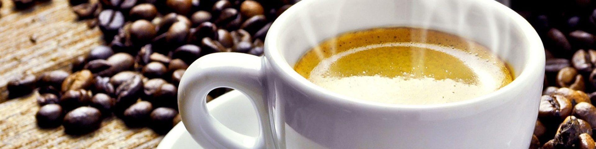 Eine frische Tasse Kaffee und Kaffeebohnen im Hintergrund